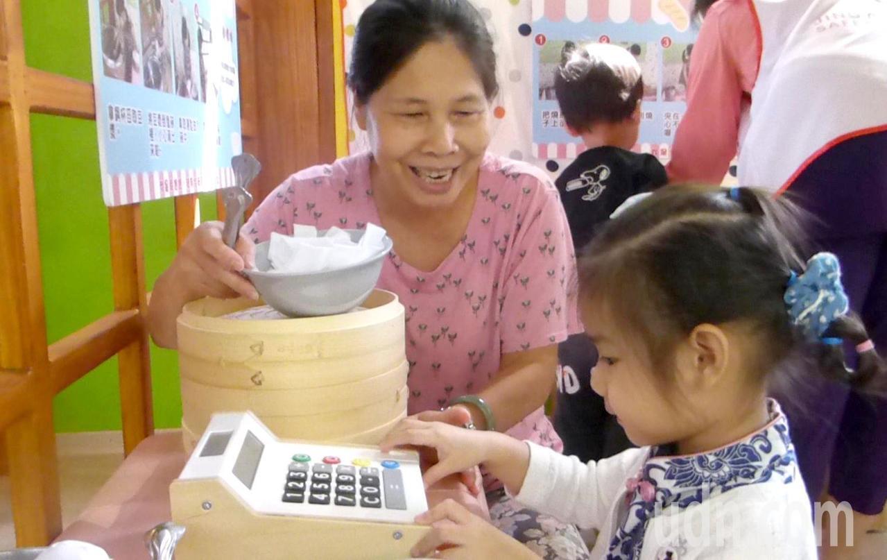 帶孫女到高雄市富民育兒資源中心活動的阿嬤透過遊戲教孩子算早餐費。記者楊濡嘉/攝影
