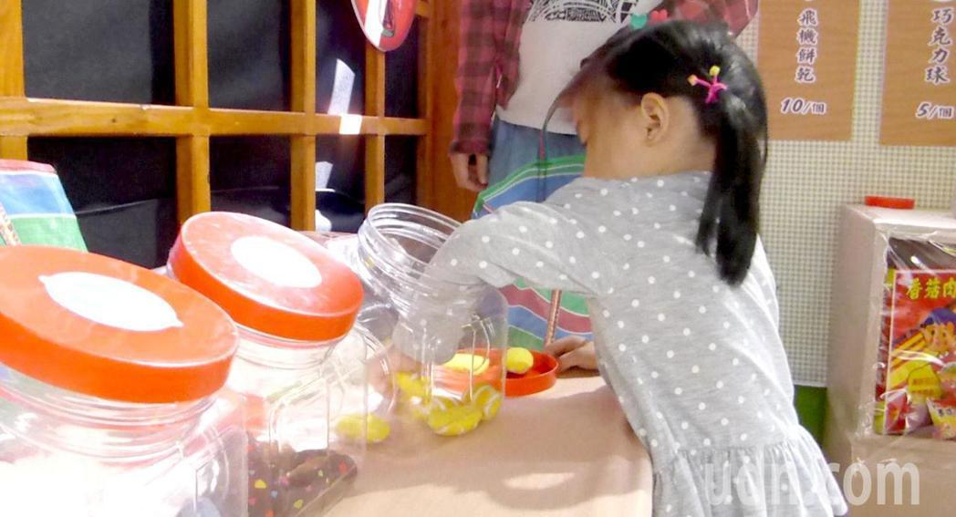 到高雄市富民育兒資源中心「柑仔店」的小朋友伸手進糖果罐選拿糖果。記者楊濡嘉/攝影
