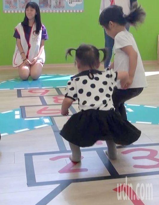 姊姊牽著妹妹在高雄市富民育兒資源中心裡「跳房子」。記者楊濡嘉/攝影