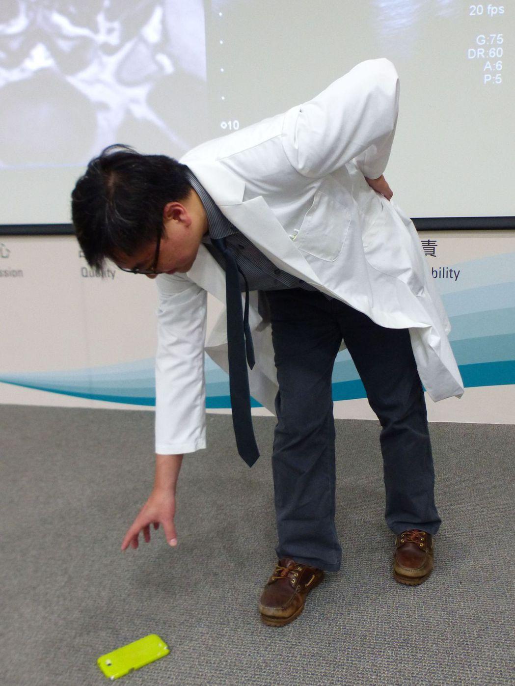 醫師蔡昇亨示範,民眾常因扭腰、彎腰拿手機造成腰椎受傷。記者趙容萱/攝影