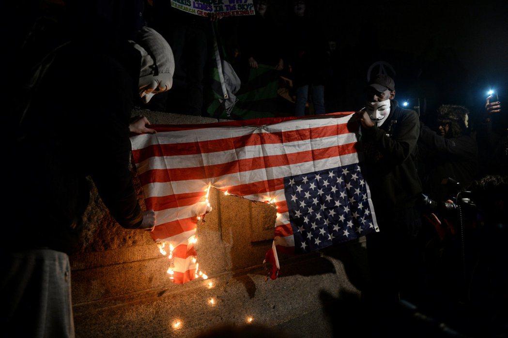 蒙面抗議群眾在倫敦特拉法加廣場,焚燒美國國旗抗議。 (路透)