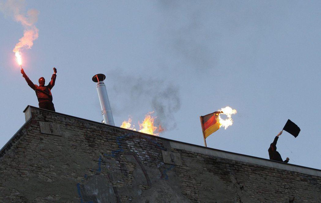 左派示威人士在柏林一棟房屋的屋頂,焚燒德國國旗抗議。 (路透)