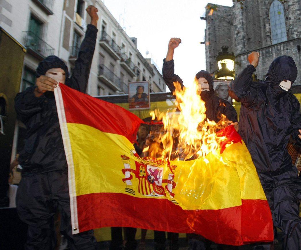 分離主議抗議人士在巴塞隆納示威,燒毀西班牙國旗。 (路透)