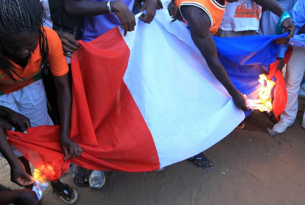 抗議群眾焚毀法國國旗。 (路透)