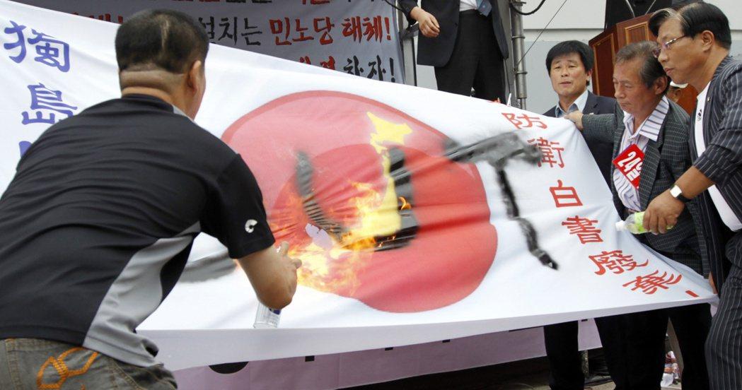 南韓保守黨人士及右翼團體成員,毀損日本國旗。 (路透)
