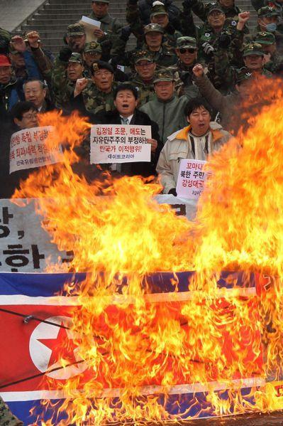 南韓民眾在北韓國旗上塗鴉並點火燒毀。 (法新社)