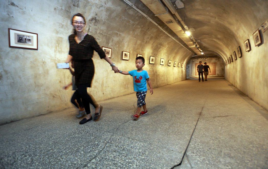 中山大學在祕境隧道舉辦「校園歷史特展」,親子攜手彷彿走過時光隧道。 記者劉學聖/...