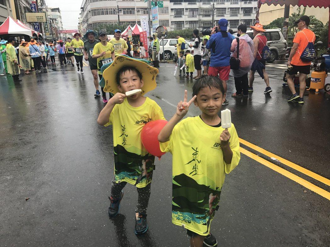 少全家總動員跑田中馬拉松,小朋友雨中一邊啃冰棒一邊跑,好開心。 記者林宛諭/攝影