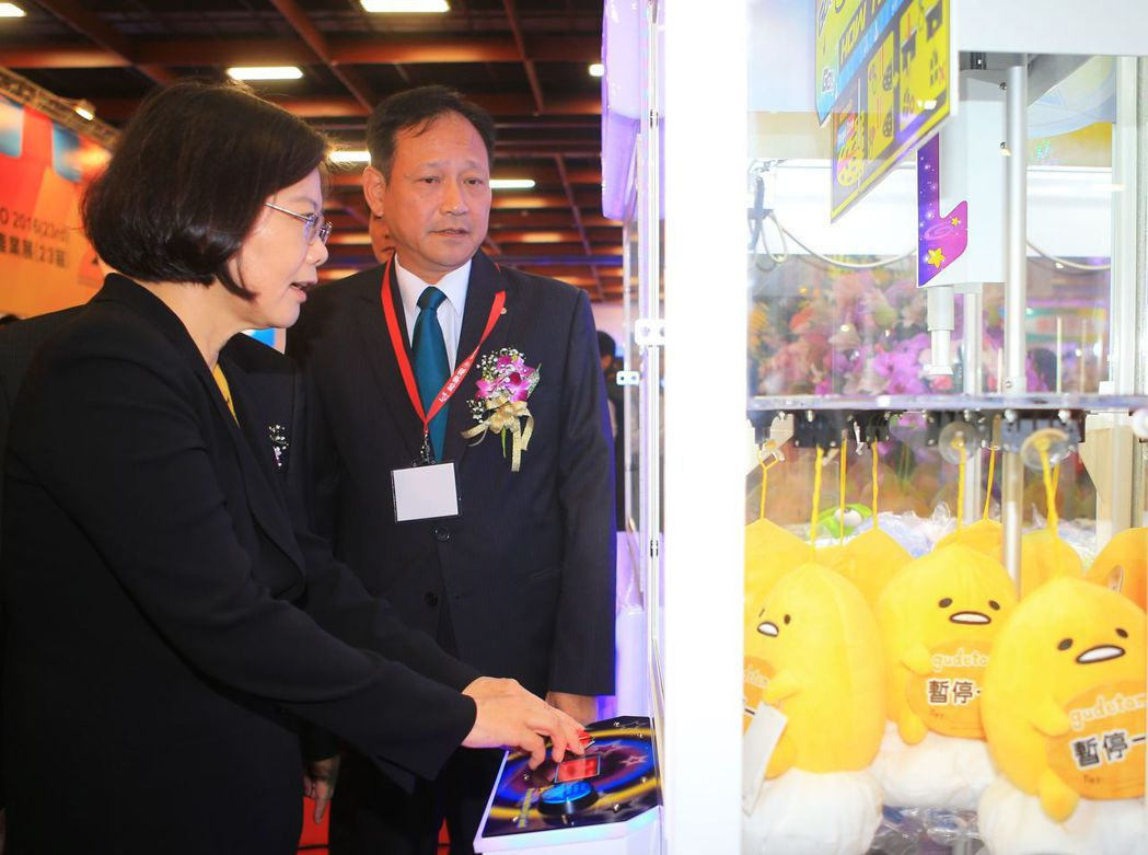 蔡英文總統(左)去年4月就職前,出席台灣電子遊戲機國際產業展,在展場玩夾娃娃機。...