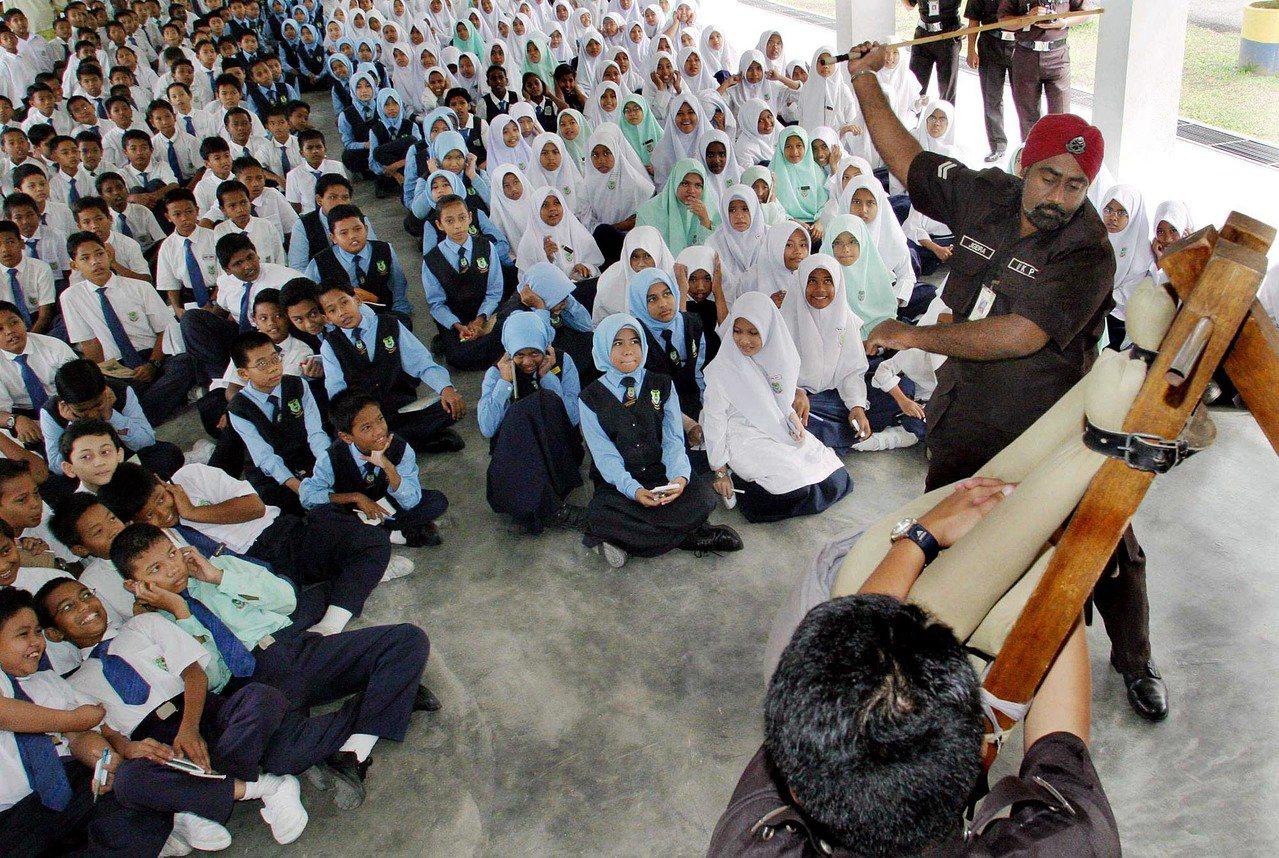 鞭刑是否能有效地制止犯罪?图为2004年马来西亚警员对国小生展示如何对罪犯施予鞭...
