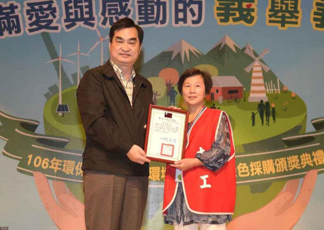 台北市副市長鄧家基頒發一等環保獎章得獎人給李秀春女士。