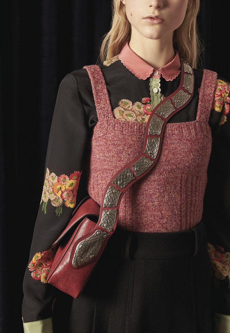 仿舊處理的復古金、銀弧形金屬鱗片服貼釘飾於波浪狀的背帶上,銜接包款的那一方更以蛇...