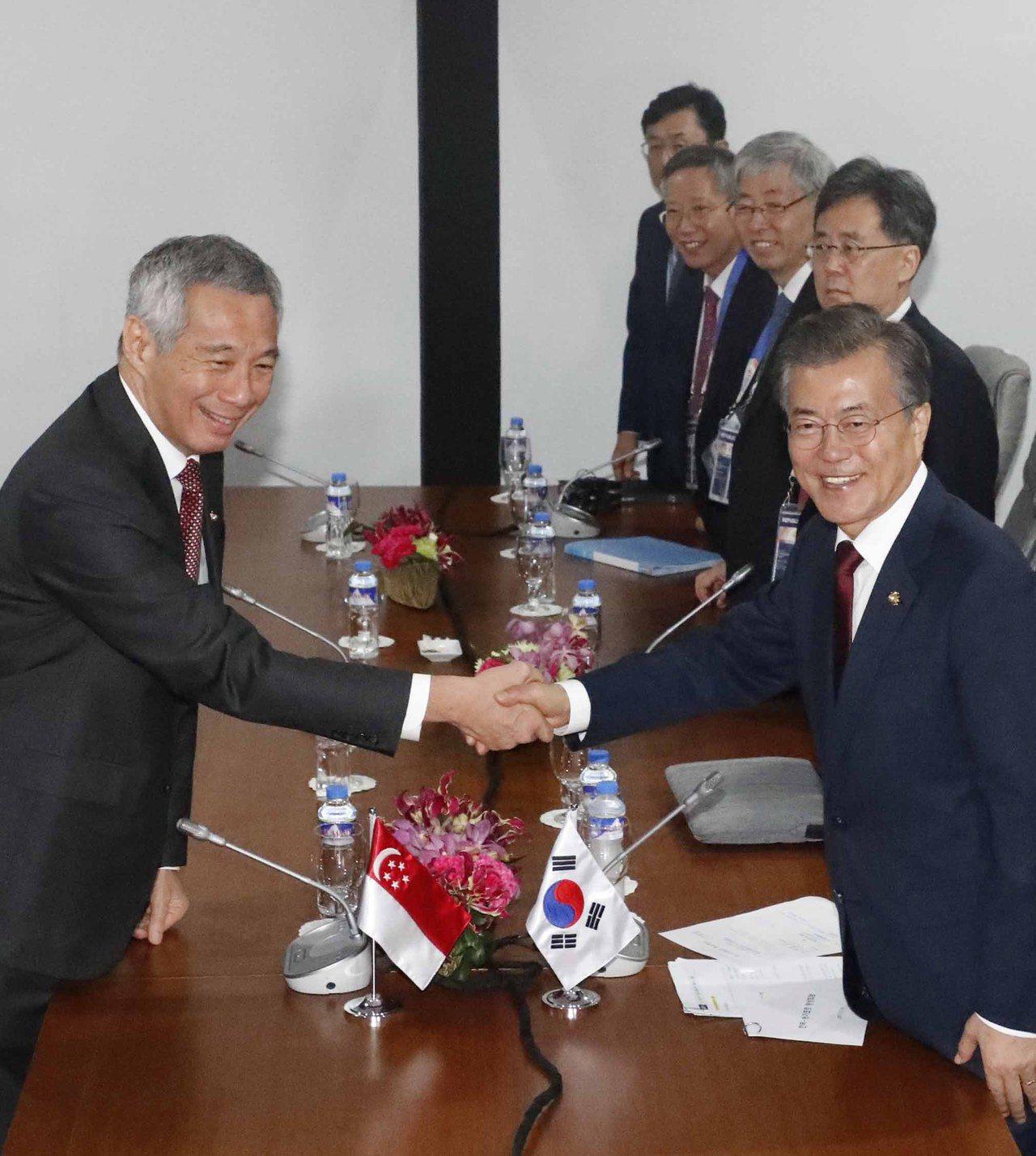 新加坡總理李顯龍(左)14日在東亞峰會與南韓總統文在寅(右)握手。歐新社