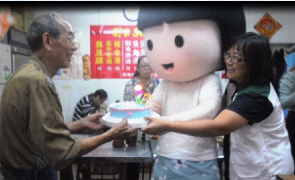 劉家臭豆腐老闆劉清山(左)昨生日當天一日所得捐給貧童,家扶中心送蛋糕給他慶生。記...