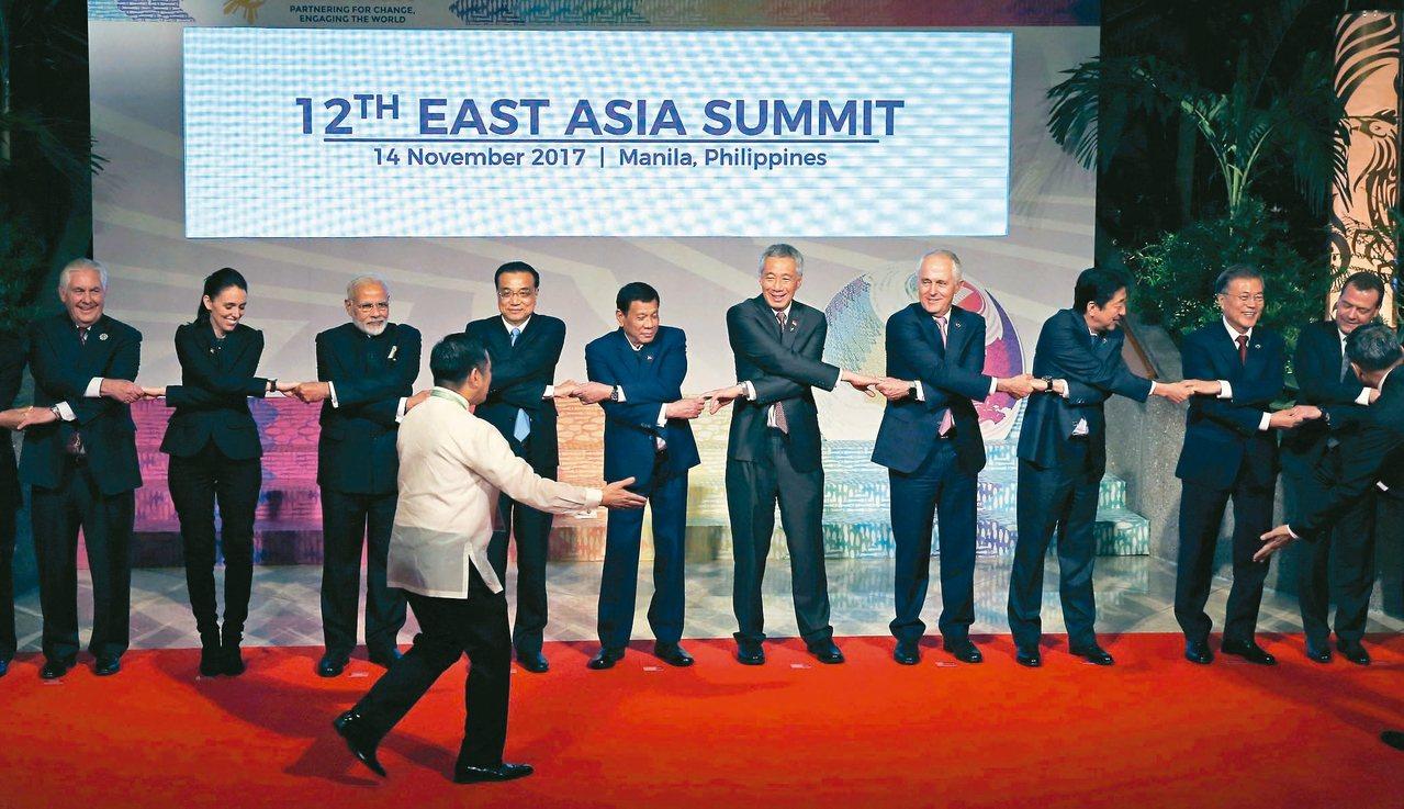 美國國務卿提勒森(左一)十四日代表總統川普出席東亞峰會,工作人員協助與會領袖交叉...