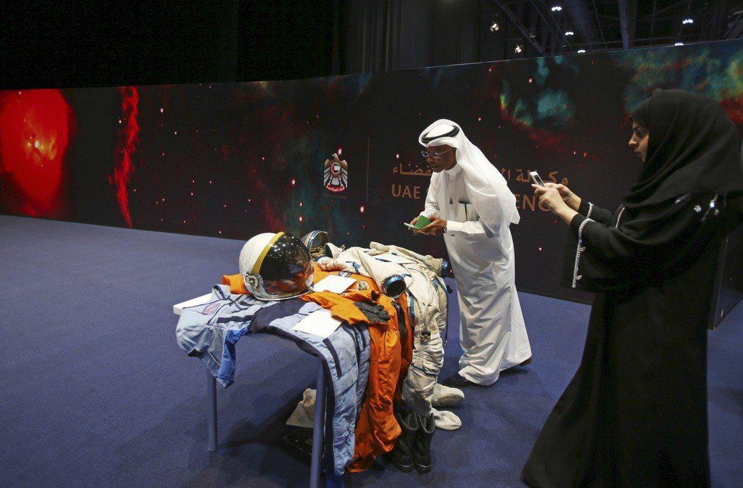 民眾在阿布達比太空博物館參觀,拍下太空人穿的衣服。 美聯社