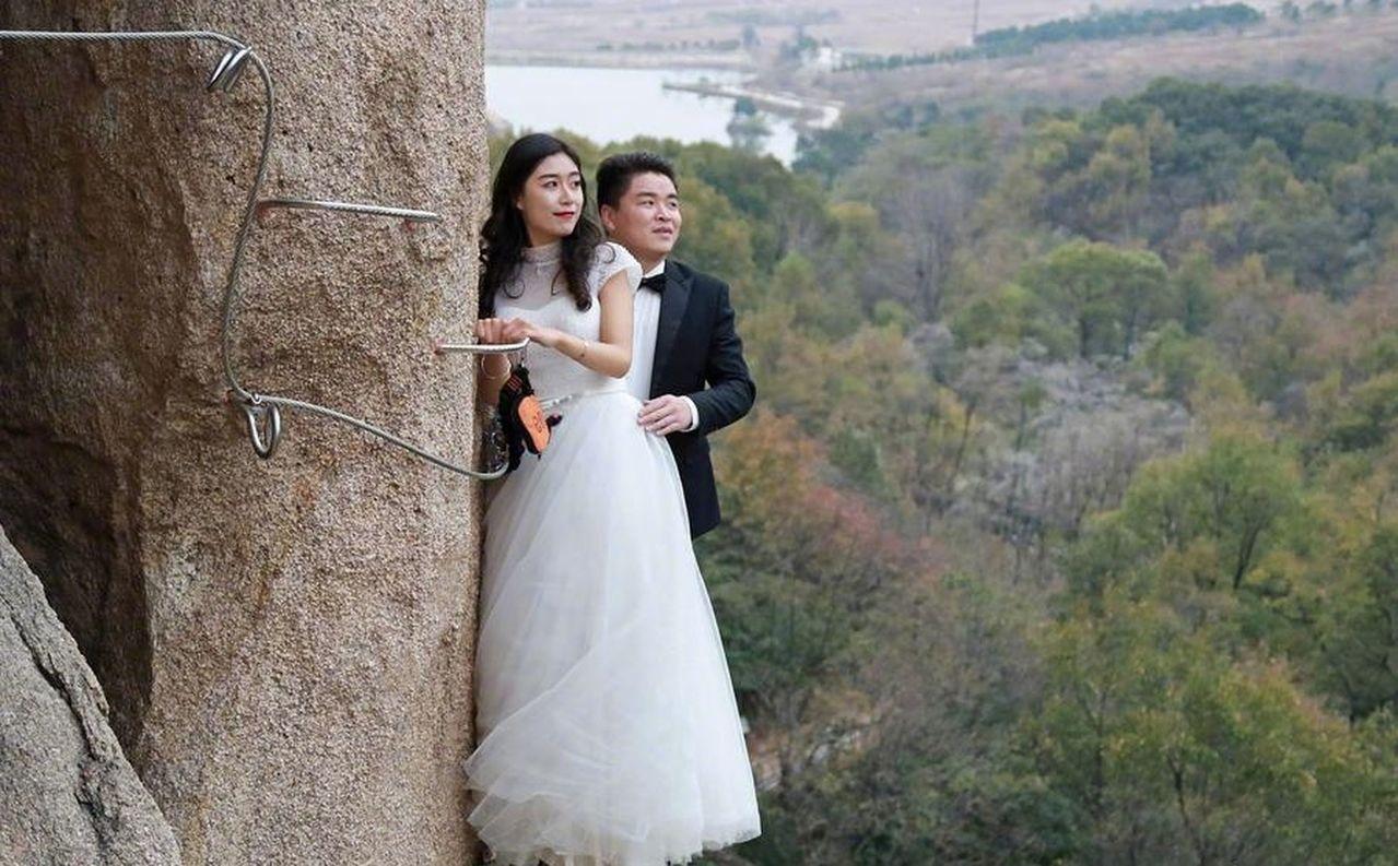 為了能拍下與眾不同的婚紗照,中國河南遂平縣一對新人日前到駐馬店岈山風景區,爬上1...