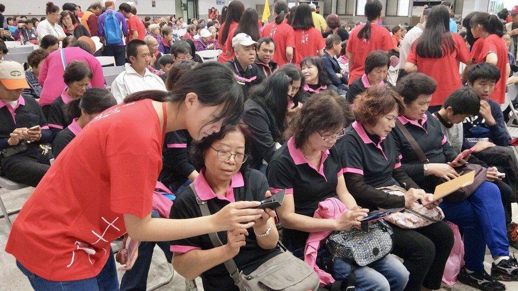 長輩們與年輕學生交換使用手機的心得。圖/桃園市青年事務局提供