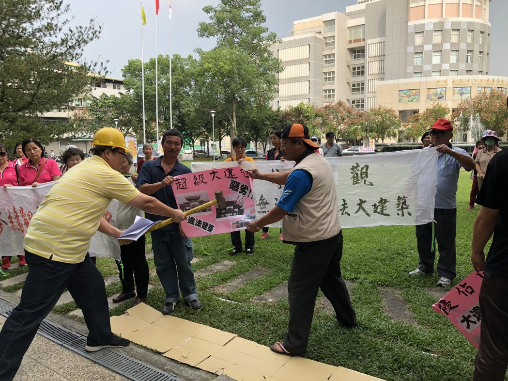 40多名草屯鎮民下午到縣府抗議違建遲遲不拆,並舉起鐵鎚打掉違建照片。記者江良誠/...