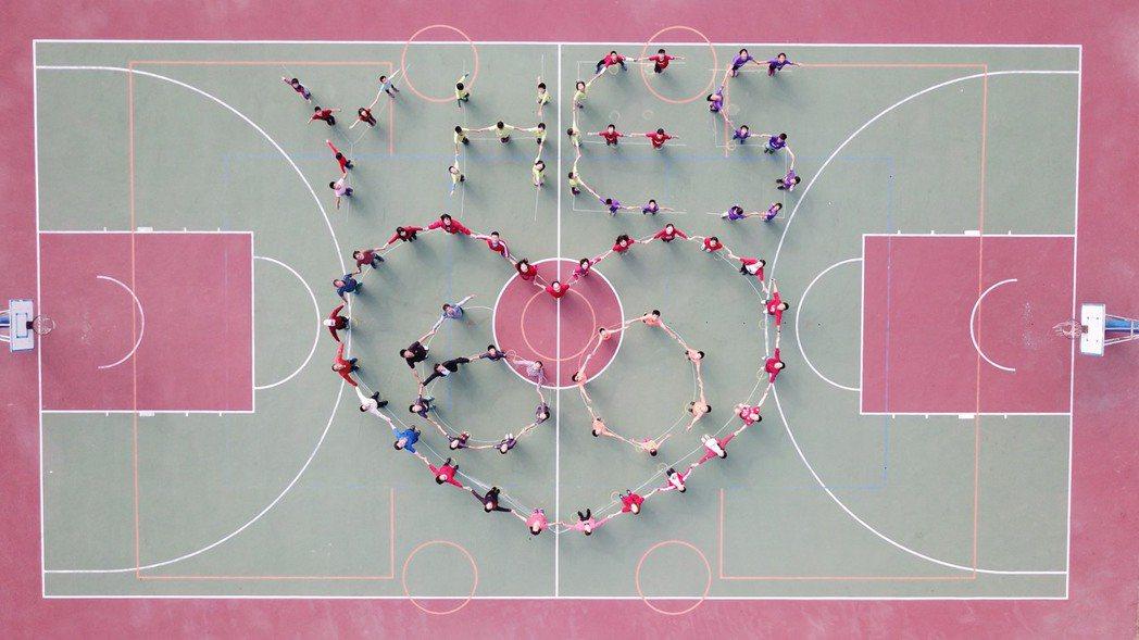 育華國小總務主任陳柏寧學以致用,今天利用空拍機拍攝學童在籃球場排字的畫面,為學校...