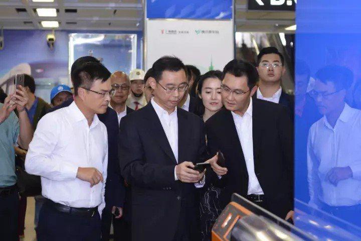 廣州市長溫國輝(中)與騰訊董事會主席馬化騰(右)用手機微信掃碼進入地鐵站。 圖/...