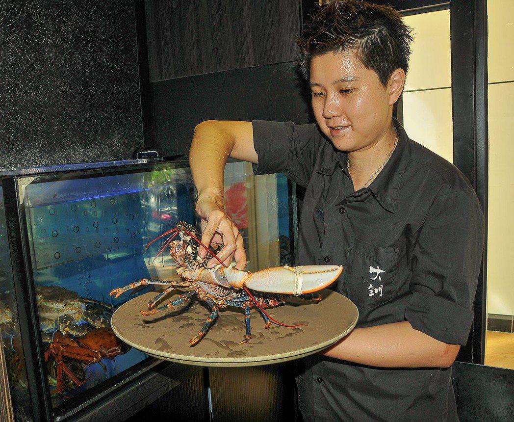 從水族箱現撈的法國藍龍蝦, 依重量有不同價格。