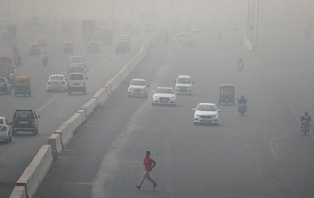 一名男子在印度德里附近霧霾籠罩的高速公路上奔跑。 路透