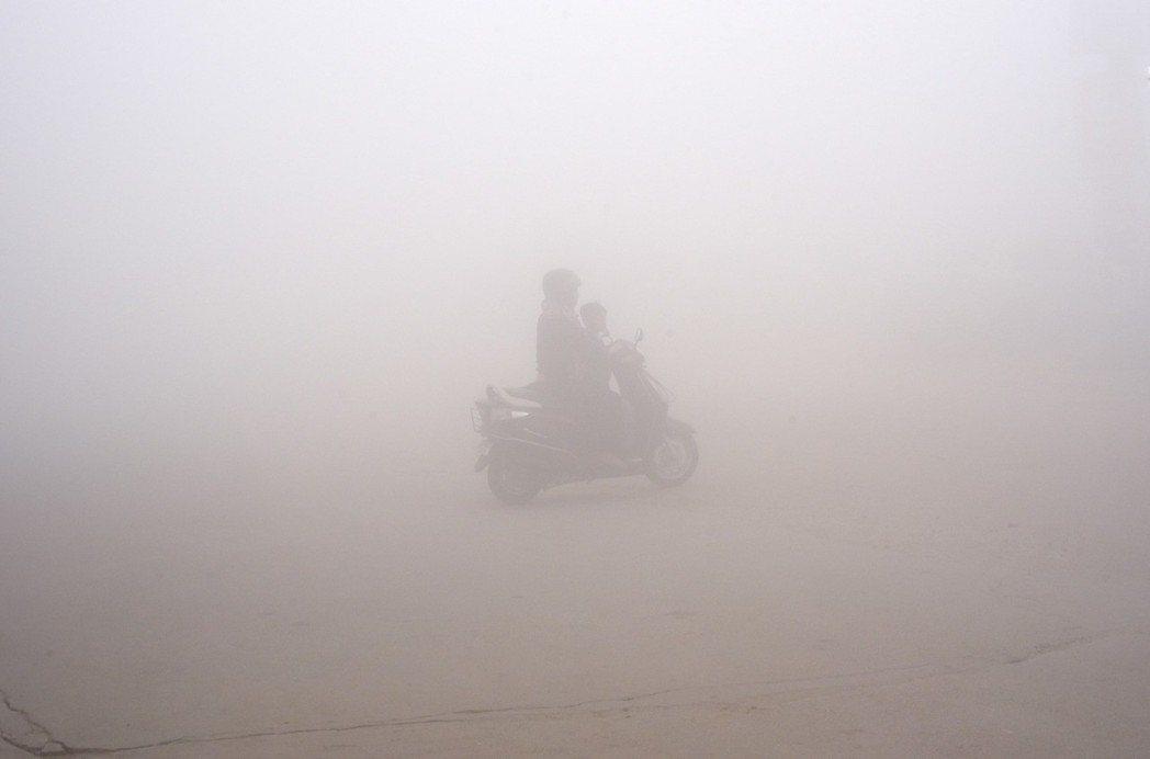 一個婦人在新德里的霧霾中騎車送小孩上學。 美聯社