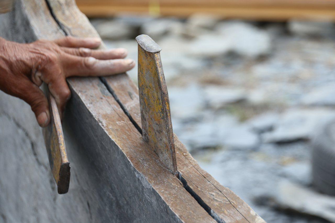 講師示範敲打石板,使用大鐵鎚將薄薄的割草機刀片打進石板岩縫隙。圖/卓溪鄉公所提供