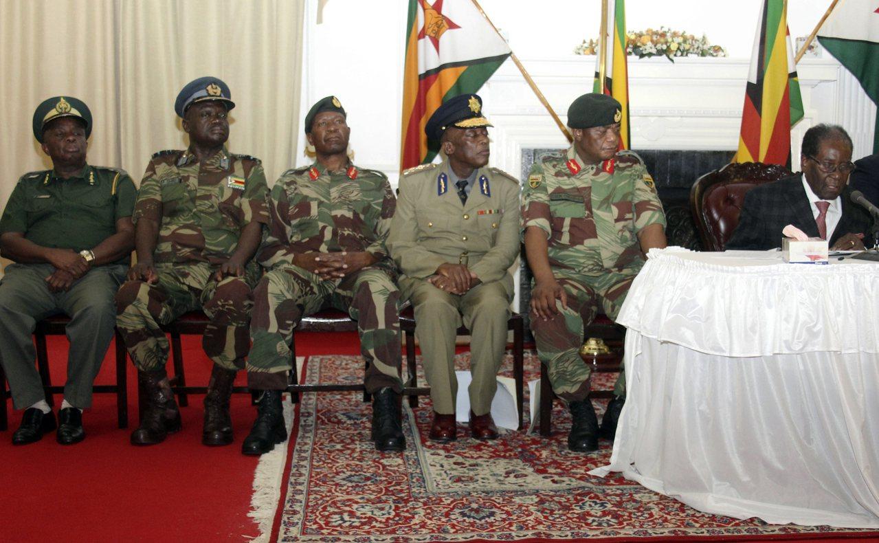 穆加比(最右側)19日在一排軍方高層陪同和監視下,發表全國電視談話。美聯社