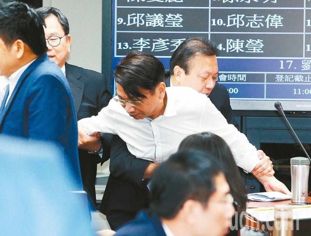 一例一休勞基法修法昨於立法院委員會初審,徐永明(中)強占質詢台近11個小時後,被...