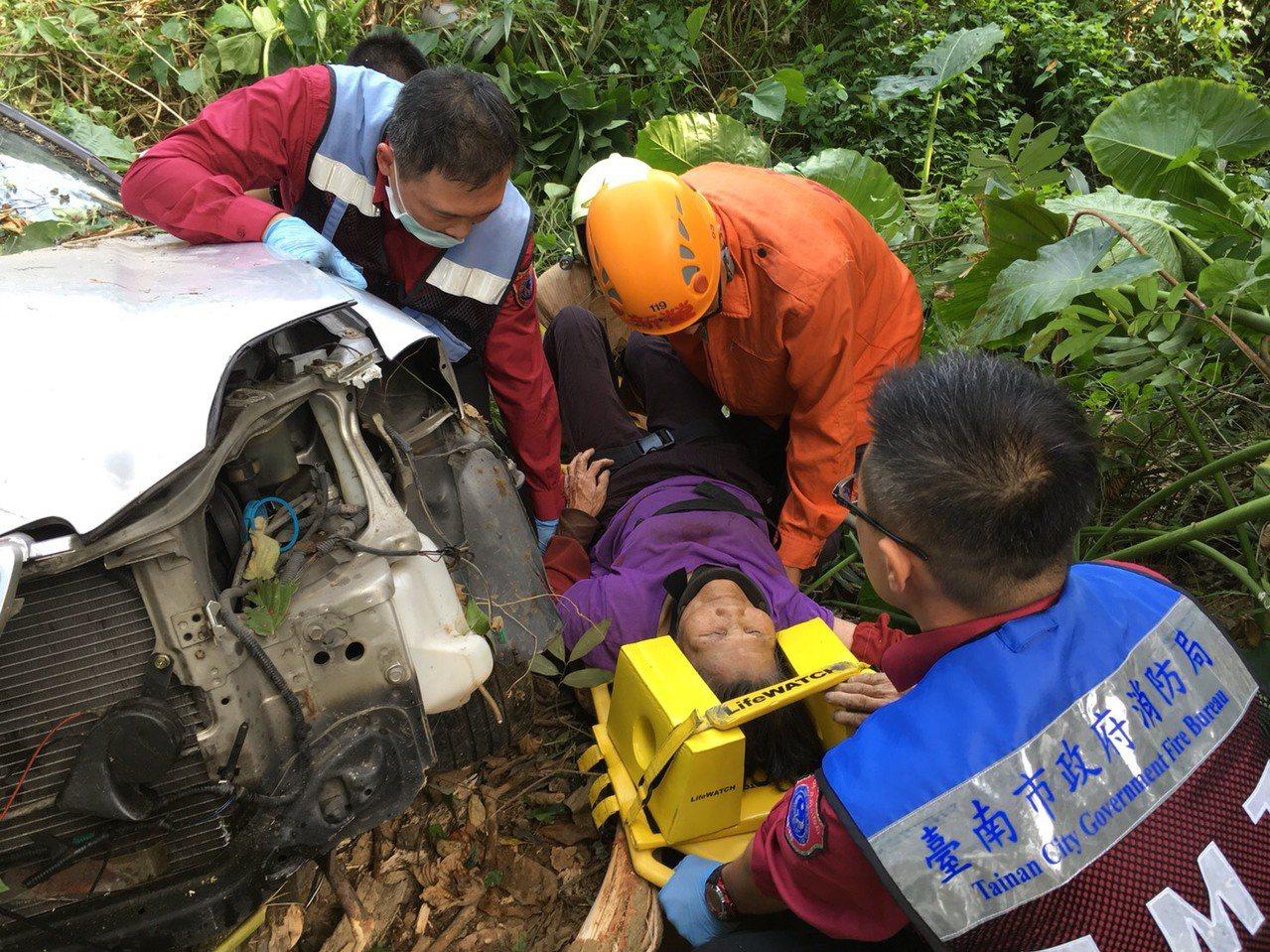 台南白河山區近午發生轎車衝入10公尺深野溪,所幸僅受輕傷,消防隊員忙救護送醫。記...