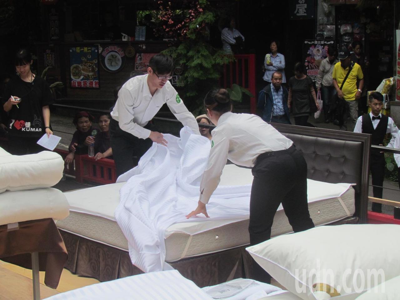 參加整床比賽的選手,動作俐落地攤開床單。記者張家樂/攝影