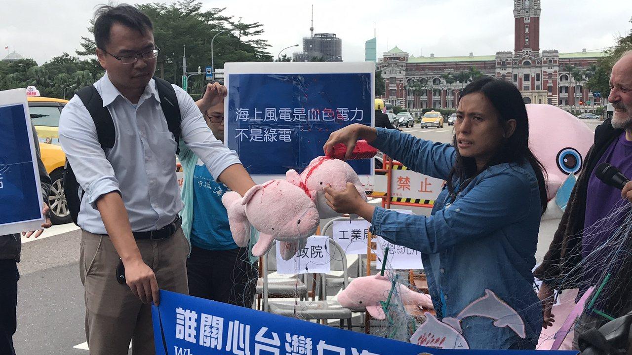 彰化縣環境保護聯盟總幹事施月英(右),憤怒地將紅漆倒在白海豚玩偶上,認為政府在殘...