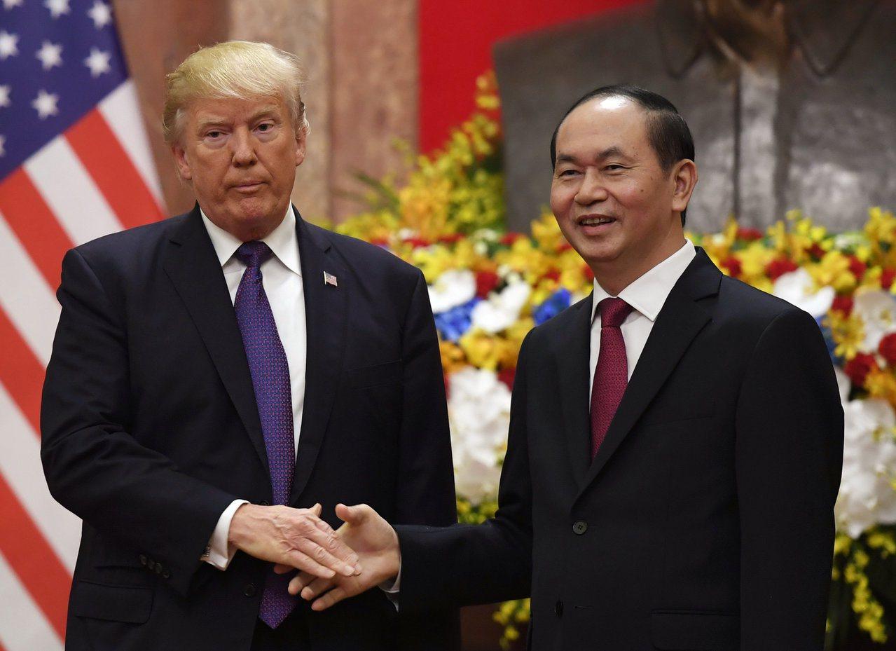美國總統川普(左)11月13日訪問越南時,與越南總統陳大光握手致意。(路透)