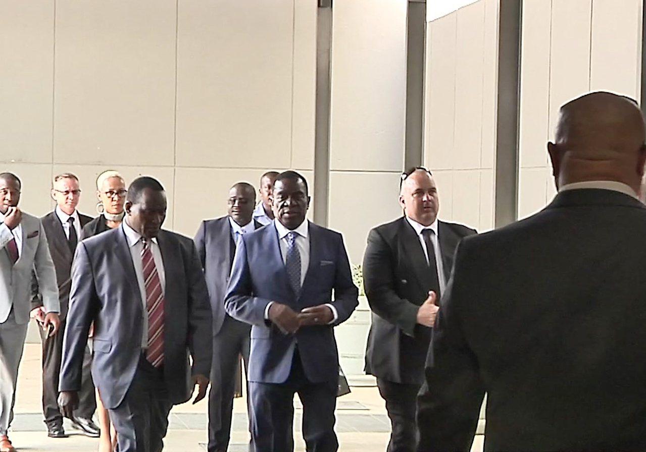 24日將就任總統的辛巴威前副總統姆南加瓦(中者)22日在南非約翰尼斯堡的機場準備...