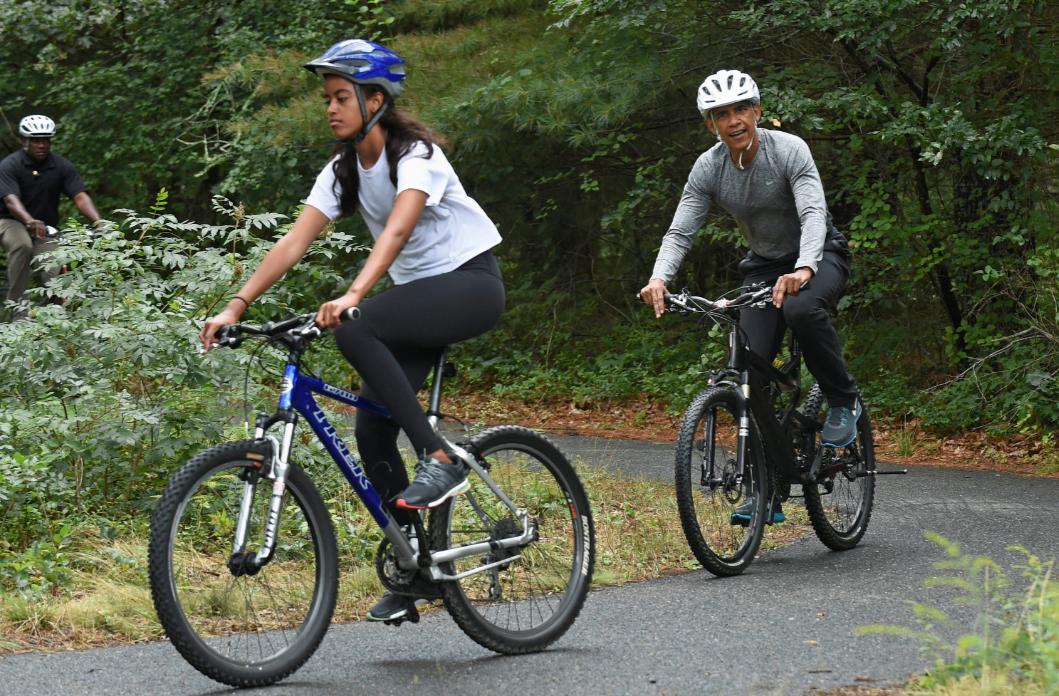 歐巴馬(後)與長女瑪莉亞(前)在西蒂斯伯里郡騎單車。美聯社