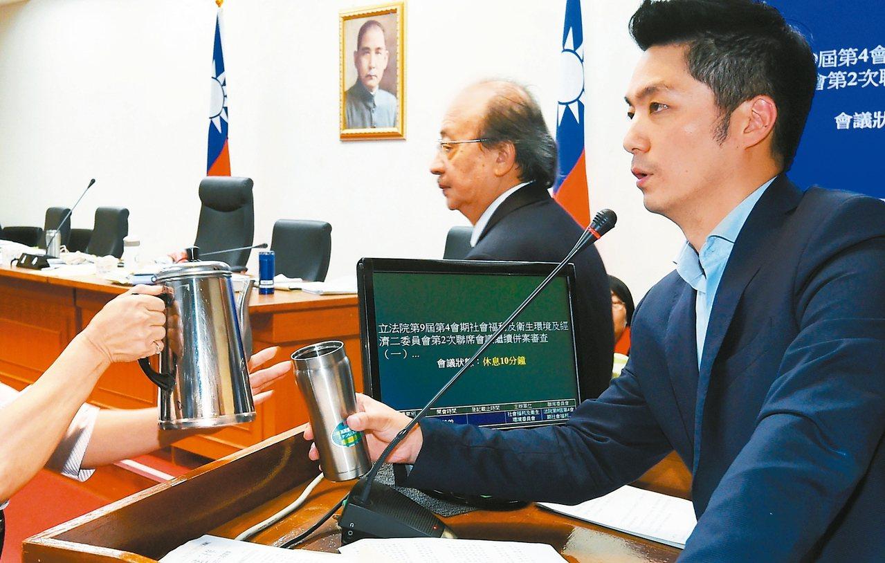 國民黨立委蔣萬安(右)昨天發言超過二個小時,在議場服務人員幫忙倒茶水後,持續發言...