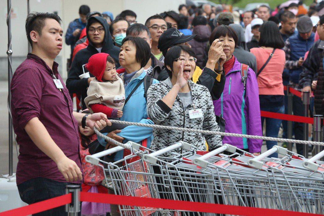 好市多黑色購物節登場,台北內湖店外民眾昨天一早大排長龍搶便宜,工作人員分段管制分...