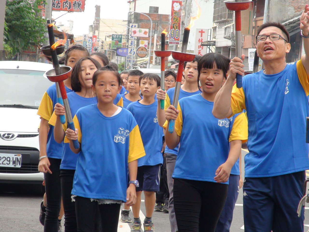雲林縣林內國小將於下周慶祝創校一百周年,今天全校師生舉著聖火繞鄉一周,向鄉民報告...
