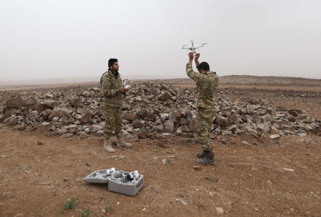 敘利亞叛軍的兩名戰士在對抗政府軍時使用無人機。 (法新社)