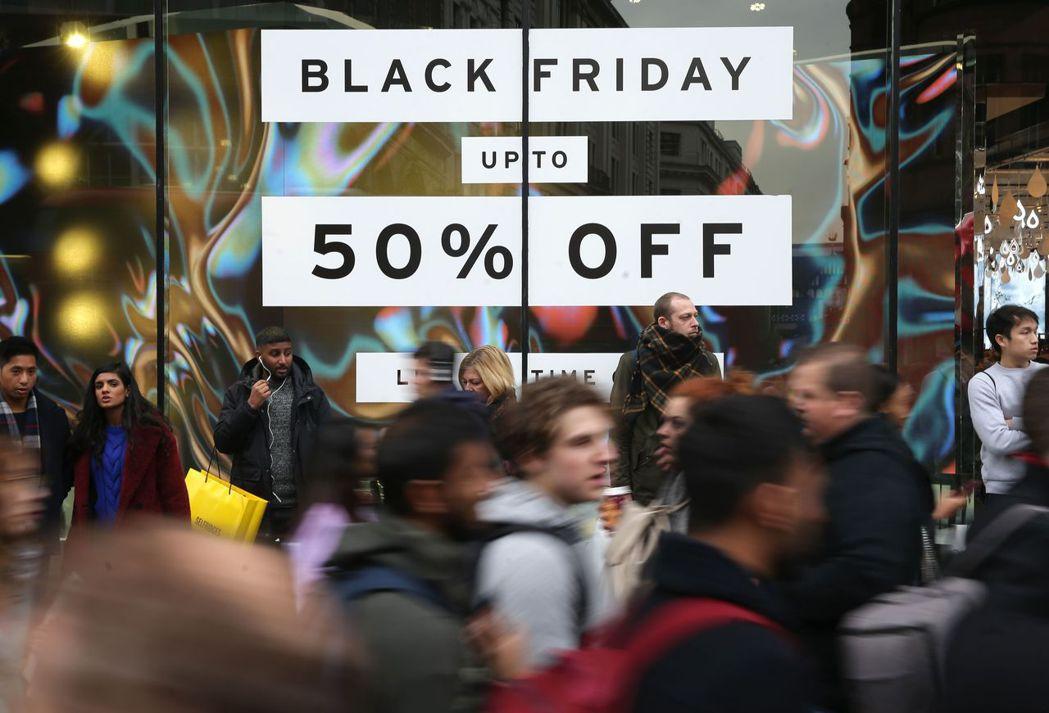 英國倫敦牛津街掛出「黑色星期五 最低五折」的看板,許多民眾也上街搶便宜。 (法新...