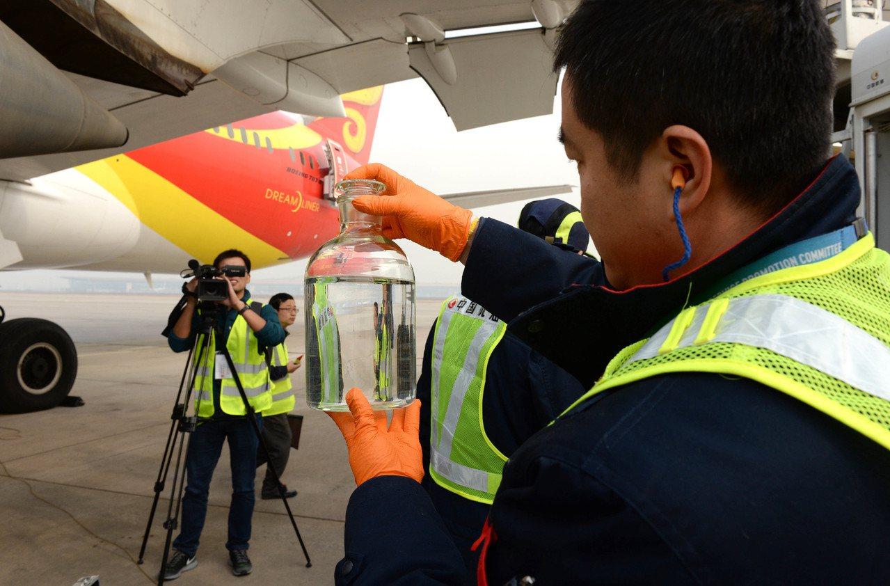 工作人員在海南航空HU497航班的波音787客機前展示生物航煤。新華社