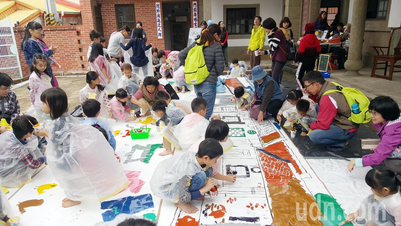 30名小朋友在陳家古厝的稻埕上一起彩繪竹南地區「最大的」一塊畫布,玩得很盡興。記...