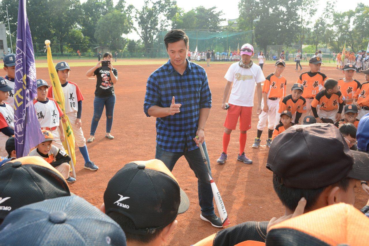 富邦悍將隊高國輝(中)受邀在徐生明少棒賽的棒球教室指導小朋友,在球隊秋訓結束後,...
