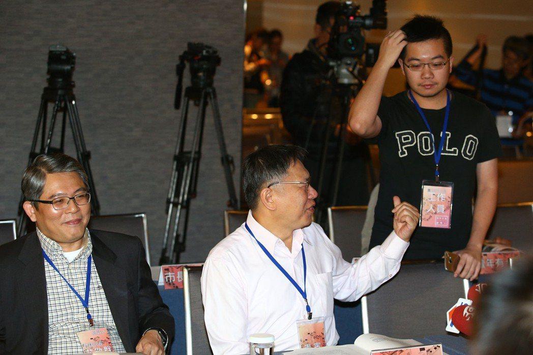 台北市長柯文哲(中)出席居住正義論壇,被一旁的幕僚緊盯不能受訪發言,他開玩笑說幕...