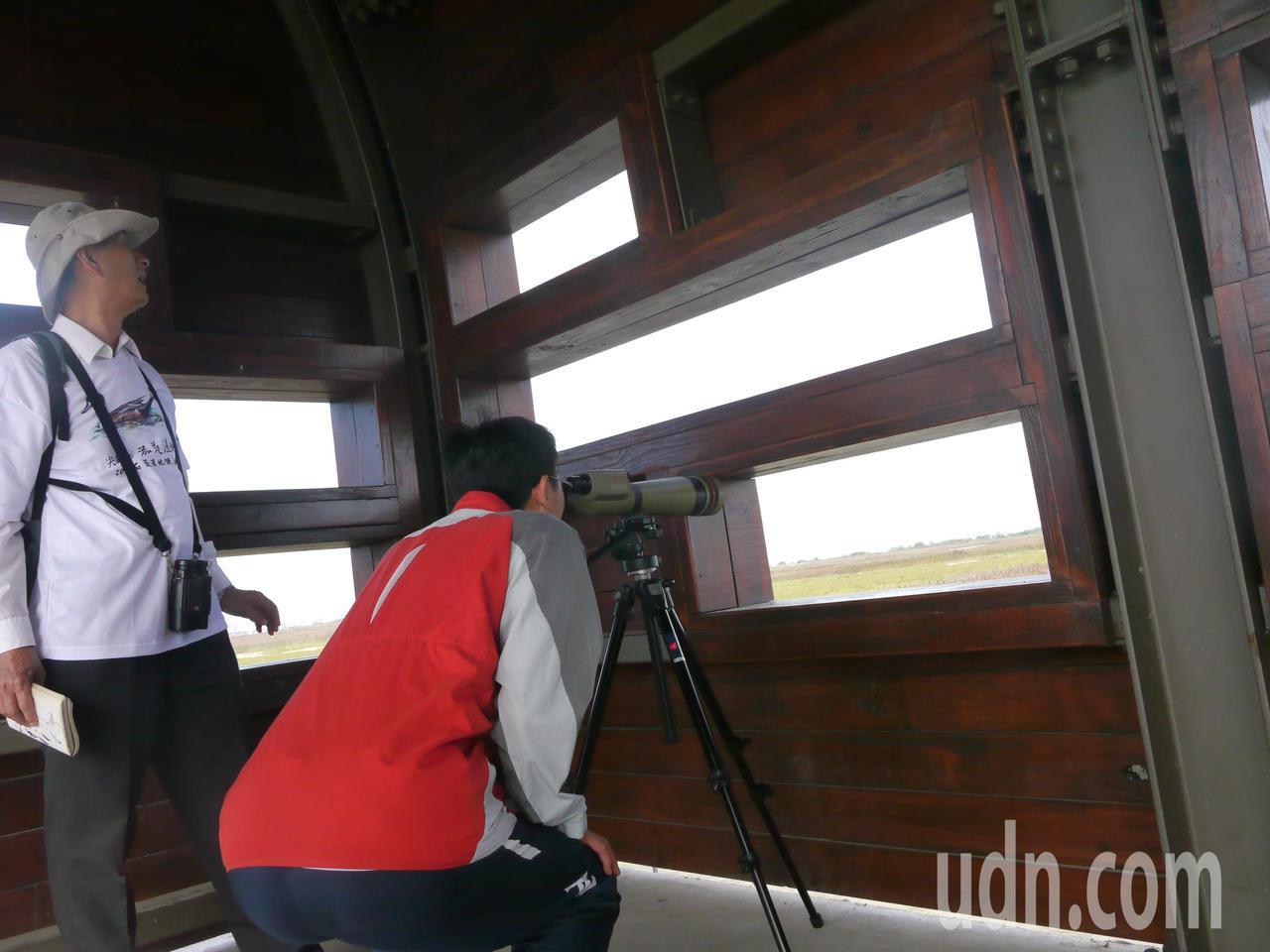 賞鳥志工(左)在賞鳥亭架設望遠鏡,讓賞鳥遊客透過鏡頭近看野鳥姿態。記者徐白櫻/攝...