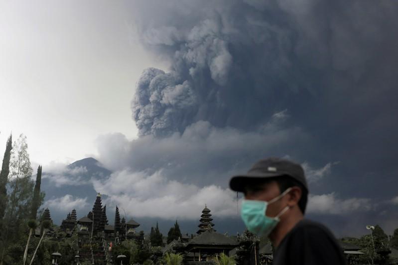 峇里島阿貢火山蠢蠢欲動,當地民眾戴口罩防吸入火山灰。 (路透)