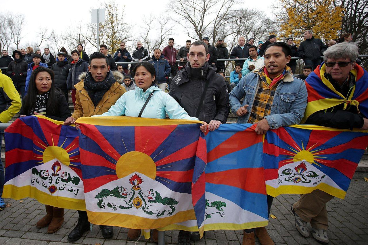 人民日報批德球場現「藏獨」旗干擾,認為體育賽場容不得政治挑釁。 美聯社