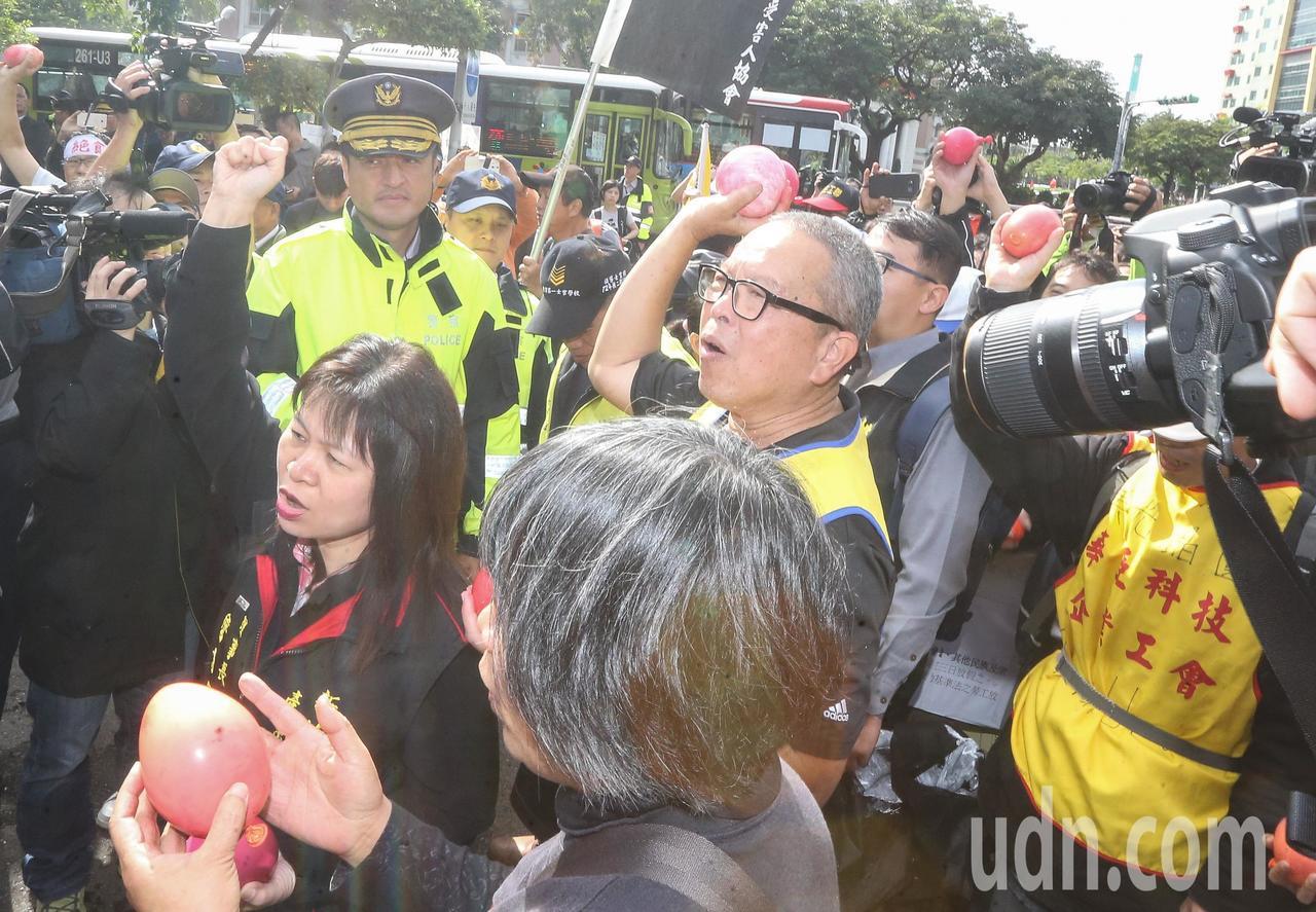 各勞團工會代表今天上午齊聚行政院前抗議,最後朝著行政院大門投擲紅色水球。記者黃威...